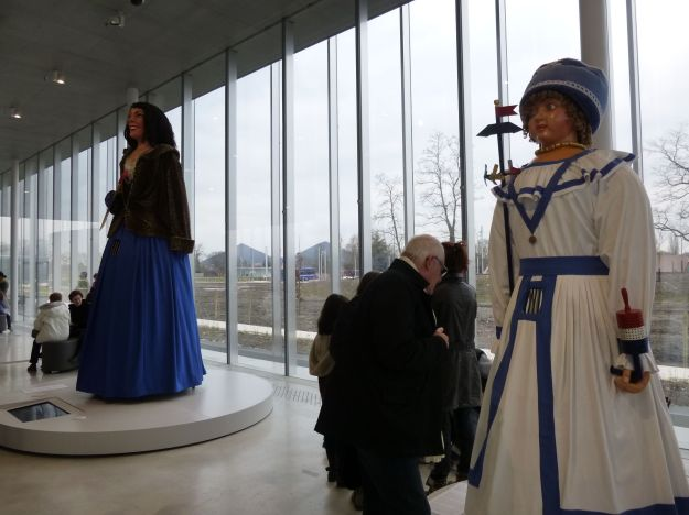 """Louvre-Lens is positioned on a former slag heap, like the two black pyramids seen between these two """"giants"""" (statues carried around Lens during festival parades)."""